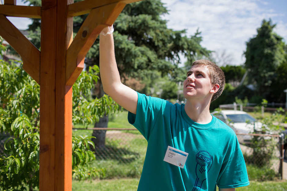 "Justin Crofoot applies stain to a gazebo during ""Circle the City with Service,"" the Kiwanis Circle K International's 2015 Large Scale Service Project, on Wednesday, June 24, 2015, in Indianapolis. (Photo by James Brosher)"