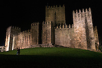 A couple walks beneath the out walls of Castelo de Guimarães, in the Minho region of northern Portugal.