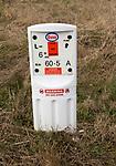 Close up of Esso gas pipeline under surveillance marker warning no dig zone, Salisbury Plain, Wiltshire, England, UK