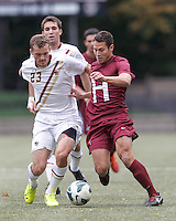 Boston College forward Cole DeNormandie (23) and Harvard University defender Ross Friedman (4) battle for the ball. Boston College (white) defeated Harvard University (crimson), 3-2, at Newton Campus Field, on October 22, 2013.