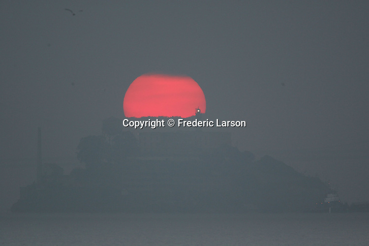 The sunrise briefly broke through the thick morning fog offering a short blast of warmth as seen over Alcatraz Island from Sausalito, California.