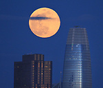 The April full moon rise between the Bank of America the Salesforce building as seen from Crissy Field, San Francisco, CA.