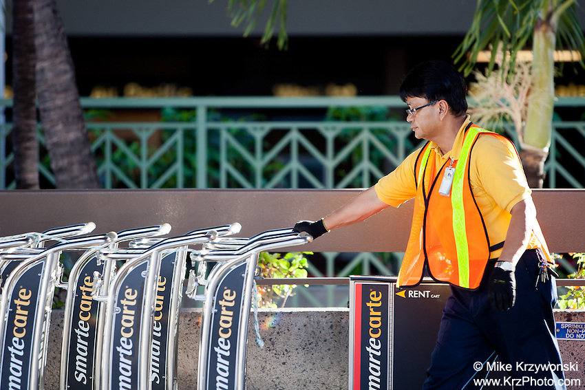 Local male airport employee maintaining luggage carts, Honolulu International Airport, O'ahu