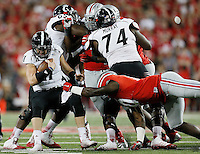 Ohio State Buckeyes defensive lineman Jalyn Holmes (10) takes down Cincinnati Bearcats quarterback Gunner Kiel (11) in the fourth quarter of the college football game between the Ohio State Buckeyes and the Cincinnati Bearcats at Ohio Stadium in Columbus, Saturday afternoon, September 27, 2014. The Ohio State Buckeyes defeated the Cincinnati Bearcats 50 - 28. (The Columbus Dispatch / Eamon Queeney)