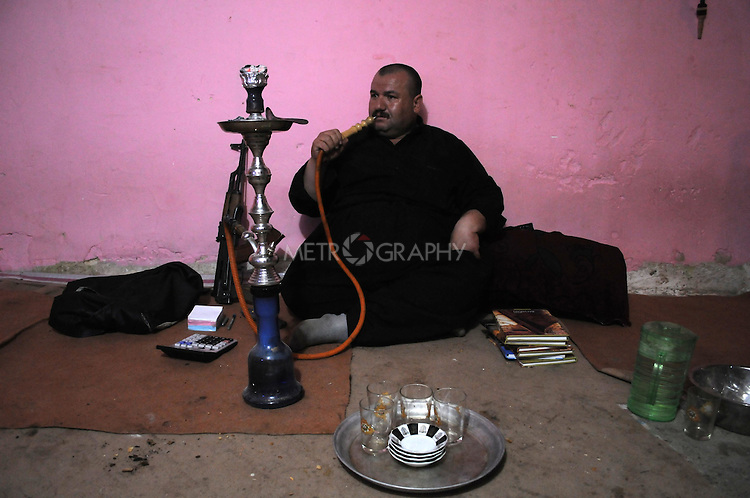 BASHMAKH, IRAQ: Tariq, the owner of a smugglers' den, smokes his shisha pipe as he waits for the smugglers to arrive...Iranian Kurdish smugglers traffic petrol from Iran into Iraq and alcohol from Iraq into Iran.  On foot, a smuggler can look to make around $10 per trip whereas with a horse a smuggler can make $100.  The routes are very dangerous with the risk of stepping on land mines or  being shot by the Iranian military..Photo by Kamaran Najm/Metrography