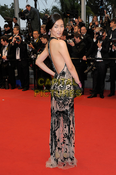 Guest.'Amour' screening at the 65th  Cannes Film Festival, France 20th May 2012.full length black pink print halterneck dress backless clutch bag side looking over shoulder .CAP/PL.©Phil Loftus/Capital Pictures.