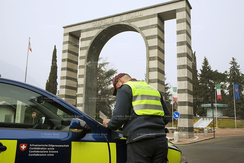 Italy. Lombardy region. Campione d'Italia. A swiss customs officer is checking the identity card (ID) of an italian citizen during a road control at the border between Switzerland and Italy. The Arch is the main entrance to Campione d'Italia which is occupying an enclave within the Swiss canton of Ticino. Swiss and italian flags. 28.02.2008  © 2008 Didier Ruef