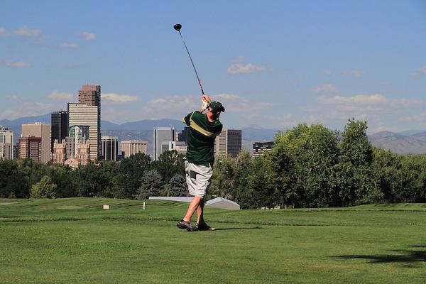 Caucasian man teeing off at City Park Golf Course, downtown skyline, Denver, Colorado, USA