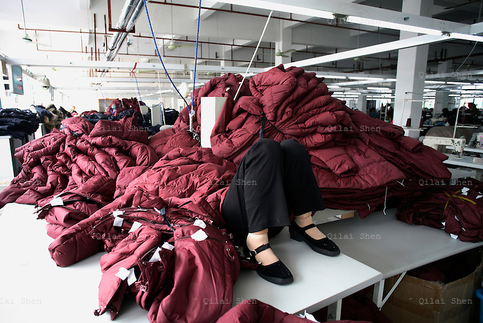 A worker takes a nap during lunch break at the Quanli Garment Factory in Pinghu, Zhejiang Province, China on October 7th, 2008.