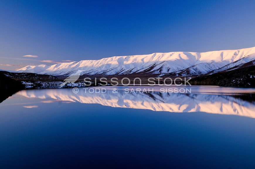 The Hawkduns, covered in snow, reflected in Falls Dam, sunset, Central Otago, South Island, New Zealand - stock photo, canvas, fine art print
