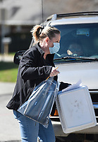 """Principal Anita Turner carries a Chromebook to hand to a parent, Saturday, March 21, 2020 at Northside Elementary School in Rogers. Check out nwaonline.com/200322Daily/ for today's photo gallery.<br /> (NWA Democrat-Gazette/Charlie Kaijo)<br /> <br /> School administrators gave out Chromebooks to parents of Northside students as an alternative method of instruction. In addition, the student packets included paper and pencil copies of lessons. <br /> <br /> It was the second day of the Chromebook distribution. On Friday, administrators distributed 125 Chromebooks.<br /> <br /> The Chromebook will allow students to join a google meet up where they can communicate with their teachers and classmates and hold online lessons. However, the online lessons will not be required as a way to remain flexible with families' schedules. <br /> <br /> """"Were trying to be very flexible because we know different families have different situations,"""" said principal Anita Turner.<br /> <br /> On March 30th, teachers and administrators will hold a virtual professional development meeting to plan the curriculum for the nine days following spring break."""