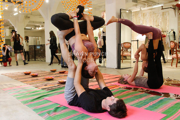 Acro yoga members execute yoga positins while wearing yogawear from the Free People FP Movement collection launch, at 218 West 40 Street New York City on May 1, 2014.