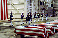 Dover, Delawre, USA, October 29,1983<br /> At precisely 7 A.M., a Marine honor guard and a color guard in ceremonial dress uniforms marched into a huge hangar at the Dover Air Force Base and stood facing 16 coffins. Behind them, suspended from the beams of the hangar, was a 38-foot American flag.<br /> The ceremony was the first on American soil honoring servicemen killed in the bombing in Beirut and the invasion of Grenada. Credit: Mark Reinstein/MediaPunch