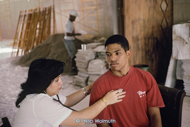 A construction worker is examined by a doctor during a workplace healthcheck.  Most workplaces receive an annual visit from a doctor and technician.  Those working with food are checked every six months.
