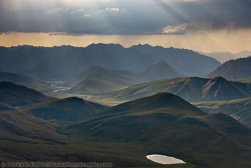 Aerial of dramatic clouds spilling light over the Philip Smith Mountains in the Arctic National Wildlife Refuge, Brooks Range mountains, Alaska.