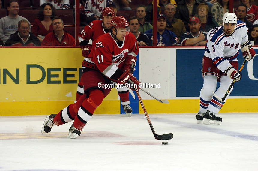 Carolina Hurricanes' Justin Williams (11) brings the puck up the ice watched by teammate Rod Brind'Amour, behind, and the New York Rangers' Michal Rozsival (3) Tuesday, March 14, 2006 at the RBC Center in Raleigh, NC. Carolina won 5-3.