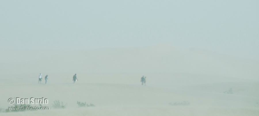 Hikers in a sandstorm at the Mesquite Flat Sand Dunes in Death Valley National Park, California
