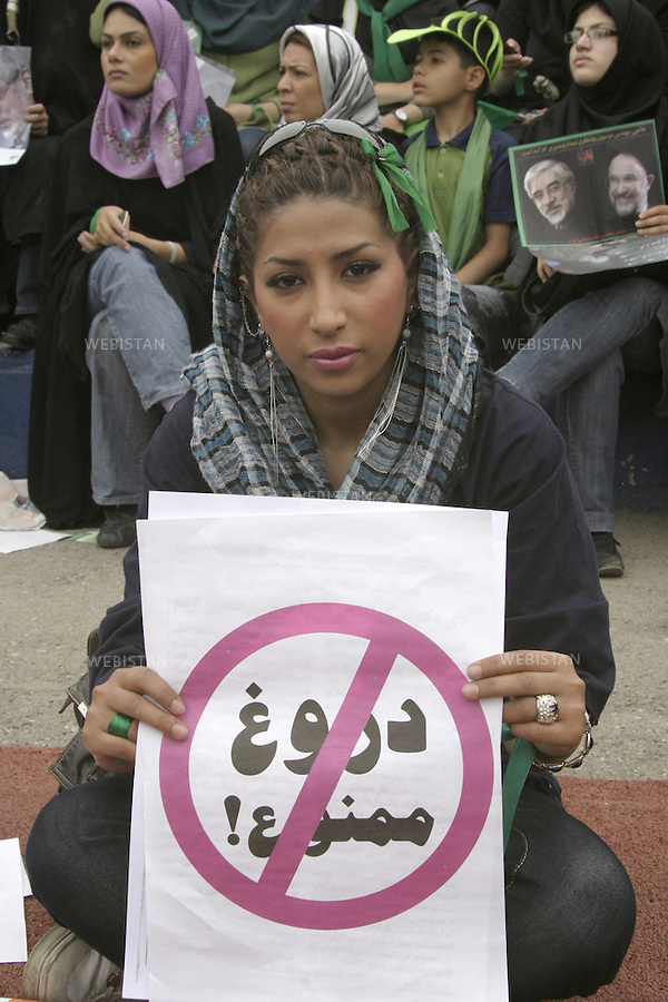 Iran. Tehran. June 10, 2009. A young woman holding a copy of largely distributed placard, reading &quot;Forbidden to Lie&quot; in Persian (Farsi), refering to allegations of deliberate distortion of figures of the state of the Nation by President-candidate Mahmoud Ahmadinejad. Group of supporters of the reformist candidate, Mir Hossein Mousavi, during a massive gathering in the streets of the Capital, two days before the election day.<br /> Iran. Teheran. 10 juin 2009. Une jeune femme avec une copie d'une pancarte largement distribu&eacute; lors de a campagne, avec l'inscription en persan &quot;Interdit de Mentir&quot;, en reference aux deformations des chiffres officiels sur l'etat du pays qu'aurait apport&eacute; le president sortant, Mahmoud Ahmadinejad. Groupe de supporters du canidat reformateur, Mir Hossein Moussavi, lors d'un rassemblement geant dans les avenues de la capitale, deux jours avant le vote du premier tour.