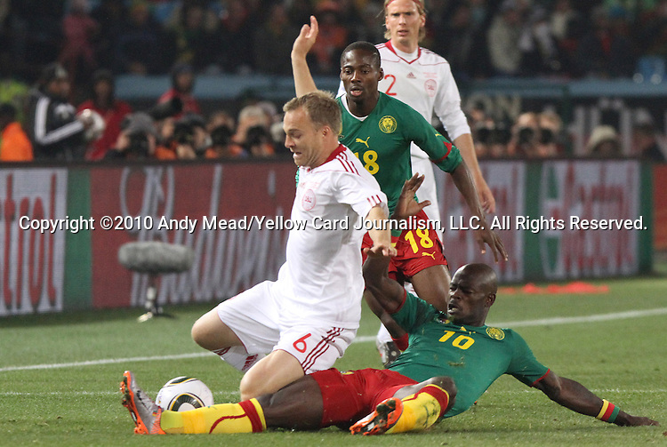 19 JUN 2010: Achille Emana (CMR) tackles the ball from Lars Jacobsen (DEN) (6) in front of Eyong Enoh (CMR) (18). The Cameroon National Team lost 1-2 to the Denmark National Team at Loftus Versfeld Stadium in Tshwane/Pretoria, South Africa in a 2010 FIFA World Cup Group E match.