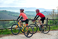 Cyclists relaxing looking at a view while road riding in the Tuscan region of Italy while on a tour of the gravel roads called Strade Bianche