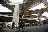 Cyclists ride their bikes. under a maze of elevated highway in Shanghai, China..23 May 2006