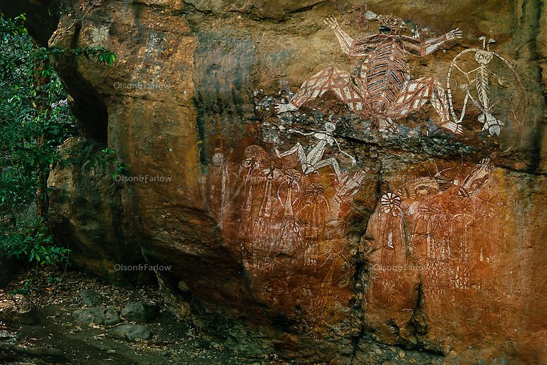 Rock art in Kakadu National Park shows Nourlanjok, (center-large figure) a Creation Anccestor and  Lightning Man or Namarrgon who is still active today. He is responsible for the violent lightning storms that occur every wet season. The band around him from his left ankle, joining his hands and head, and down to his right ankle represents the lightning he creates. He uses the axes on his head, elbows and feet to split the dark clouds and make lightning and thunder.<br /> An archaeological dig at Anbangbang rock shelter in the early 1980s revealed that Aboriginal people have been using the shelter for at least 20 000 years.