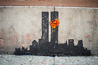 """Street art enthusiasts flock to the Tribeca neighborhood of New York on Tuesday, October 15, 2013 to see the fifteenth installment of Banksy's graffiti art, """"Tribecca"""". The elusive street artist is creating works around the city each day during the month of October and this installment shows a silhouette of the World Trade Center with a flower attached.  (© Frances M. Roberts)"""