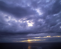 Last sun gleams through a crack in the clouds above the Atlantic Ocean seen from Cape Wrath, nw Sutherland, Scottish Highland
