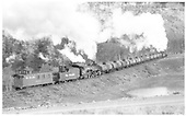 D&amp;RGW #483 pushing on 11-car tank train going up Cumbres just east of Narrows, curving around Lobato Lake.  #485 is leading.<br /> D&amp;RGW  Lobato Lake, NM  Taken by Perry, Otto C. - 6/1942