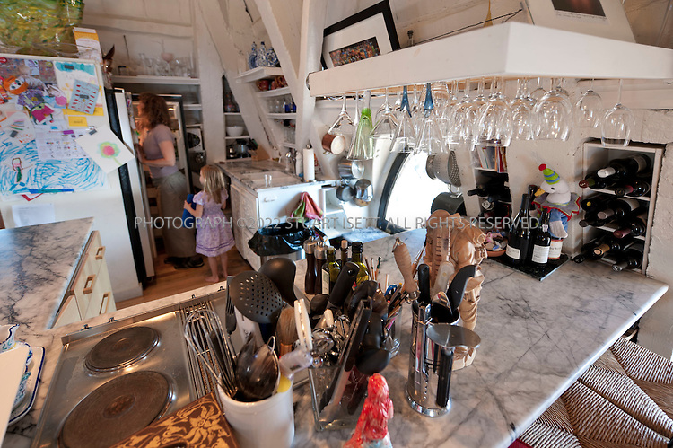 9/27/2010--Seattle,WA, USA..The kitchen on the second floor of Petra Franklin's penthouse apartment in Smith Tower in Seattle, complete. Here Petra's older daughter Simone and a family friend look in the fridge...Smith Tower, located in Seattle's Pioneer Square neighborhood, is the oldest skyscraper in the city. Completed in 1914 it has 38 floors and  remained the tallest building on the West Coast until the Seattle Space Needle overtook it in 1962. The tower is 462 ft (143 meters) from street level to the top of the pyramid with a small glass lighthouse at the top...Petra Franklin, 46 and her husband David Lahaie, 51 live in the pyramid on top of Smith Tower with their two daughters Simone, 6, and Naomi, 3. Franklin is co-founder and general partner of Vault Capital, a venture capital fund with offices in Smith Tower..Copyright © 2010 Stuart Isett. All rights reserved.