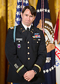 William Swenson, a former active duty Army Captain, who will be awarded the Medal of Honor for conspicuous gallantry, listens as United States President Barack Obama makes remarks in the East Room of the White House in Washington, D.C. on October 14, 2013.  Captain Swenson accepted the Medal of Honor for his courageous actions while serving as an Embedded Trainer and Mentor of the Afghan National Security Forces with Afghan Border Police Mentor Team, 1st Battalion, 32nd Infantry Regiment, 3rd Brigade Combat Team, 10th Mountain Division, during combat operations in Kunar Province, Afghanistan on September 8, 2009.<br /> Credit: Ron Sachs / CNP