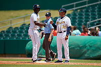 Montgomery Biscuits Jesus Sanchez (4) fist bumps first base coach Gary Redus (20) as umpire Austin Jones looks on during a Southern League game against the Mobile BayBears on May 2, 2019 at Riverwalk Stadium in Montgomery, Alabama.  Mobile defeated Montgomery 3-1.  (Mike Janes/Four Seam Images)