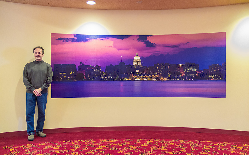 "Michael Knapstein stands next to his large-scale mural photograph installed as part of the ""Reflections:Madison"" exhibit at the Monona Terrace Convention Center."
