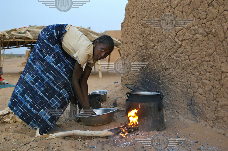 A girl prepares a meal in the village Intedeyne. Children's education remains a major challenge for Mali, which has the highest percentage of people living below the poverty line of any country in the world, with female literacy rates 50 percent lower than that of men...