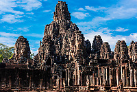 The Bayon (Angkor Thom), Shaped like a pyramid, this symbolic temple-mountain features 54 towers, bearing more than 200 serene and smiling stone faces; Angkor Wat complex, Cambodia.
