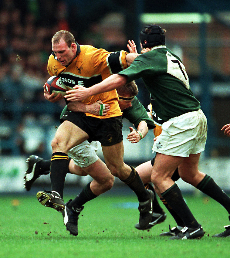 Photo. Richard Lane. .Wasps v London Irish.Tetley Bitter Cup Quarter Final.28/2/99..Lawrence Dallaglio bursts through the tackles of Ryan Strudwick and Rob Gallacher.