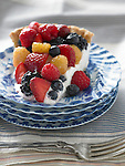 Berry pie with strawberries, blueberries, red raspberries, golden raspberries, and blackberries on a sweet sour cream filling