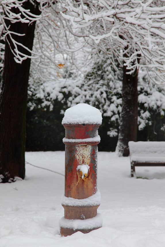 A typical drinking fountain of Rome, with the writing SPQR well readable, covered with snow. The photo is taken in villa Gordiani, in February 2012. Digitally Improved Photo.
