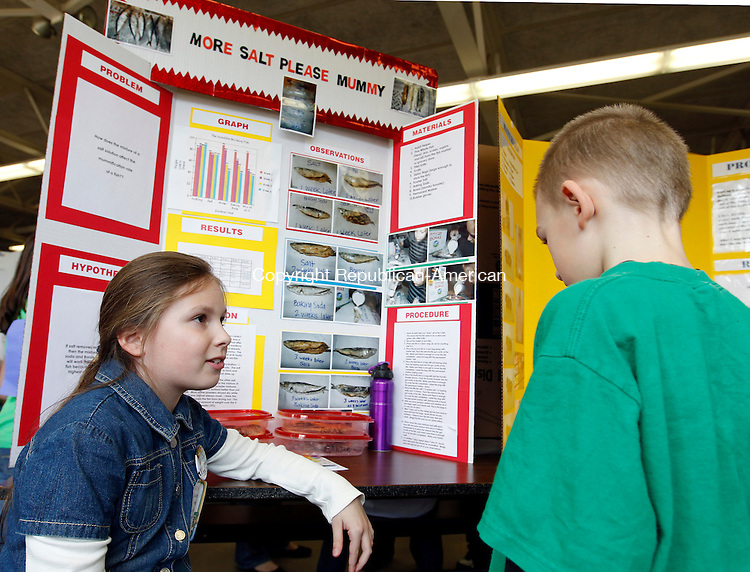 "Prospect, CT- 14, April 2011-041411CM03  Giuliana Pinevich, a third grader at Algonquin School in Prospect talks to fellow classmate, Austin Chaplen Thursday afternoon during the schools 16th annual Science Fair.  Pinevich project, titled ""More Salt Please Mummy"", tested different preservations methods of Sardines, using salt, Borax and baking soda.  She discovered a combination of three works the best. Christopher Massa Republican-American"