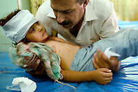 a wounded iraqi child waits for treatment at the Iarmuk hospital on May 31 2004, in the outscorts of Baghdad. the blast that wounded him  claimed to damege the road near the judgement consular. the number of casualties is uncertain but is not less then three