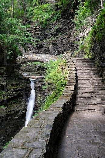 Trail ad staircase leading to stone bridge in a rocky gorge, Watkins Glen, New York, USA.