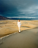 USA, California, young woman standing on sand dune, Stovepipe Wells, Death Valley National Park