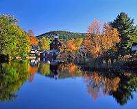 USA, New Hampshire, Old grist mill building reflecting in pond in Ashland