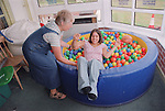 Carer assisting teenage girl with physical disability to lean backwards into ball pool in residential respite care home.  MR