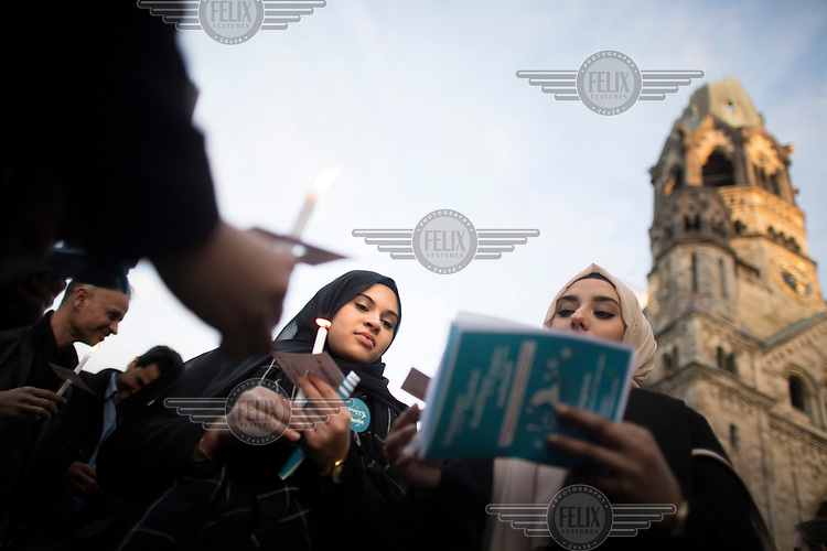 Two young Muslim women, holding candles and reading from a leaflet, during a peace rally with the slogan 'Religionen fuer ein weltoffenes Berlin' (Religions for a an open Berlin). It was held in memory of the victims of the Breitscheidtplatz Christmas market terror attack.
