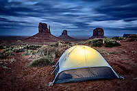 A tent, lit from within, overlooking the Mittens and Merrick Butte in Monument Valley