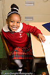Parochial School Bronx New York  Kindergarten portrait of girl sitting at desk vertical