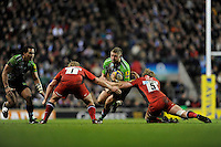 Chris Brooker of Harlequins is tackled by George Kruis (right) and Rhys Gill of Saracens during the Aviva Premiership match between Harlequins and Saracens at Twickenham on Tuesday 27 December 2011 (Photo by Rob Munro)