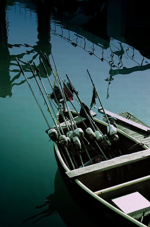 A small fishing boat with marker bouys in a harbour with reflections