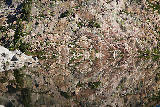 rock wall shoreline reflected in a mountain lake in the beartooth wilderness area in montana